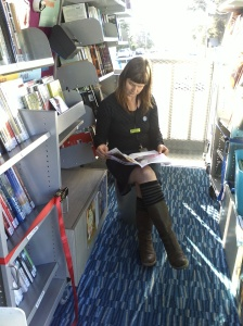 Photo of librarian Sarah reading a magazine in the Library Mobile van.