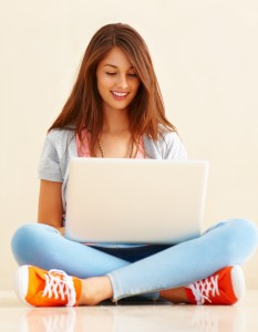 Young-lady-sitting-on-the-floor-using-her-laptop-233x300