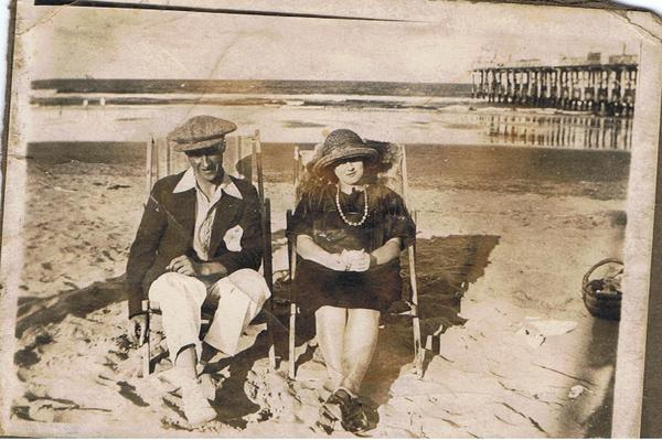 Couple sitting on beach, old Brighton pier in background
