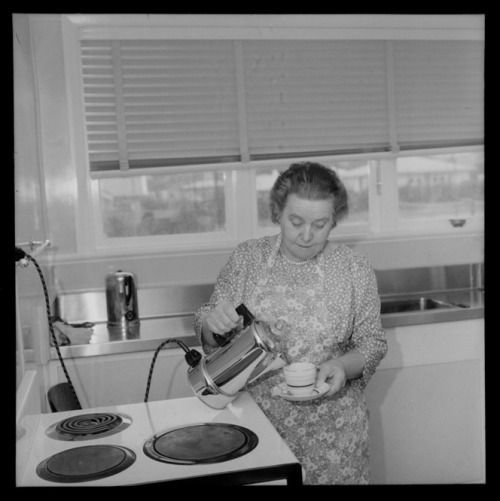 Mrs Mabel Howard, in her new house in Karori, Wellington, showing her making a cup of tea. Dominion post (Newspaper) :Photographic negatives and prints of the Evening Post and Dominion newspapers. Ref: EP/1960/0845-1-F. Alexander Turnbull Library, Wellington, New Zealand. /records/30652147